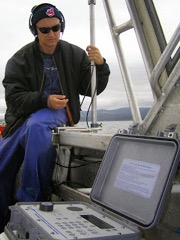 Adam Barnett listening to the pings emitted by the transmitter placed on a sevengill shark.